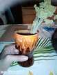 Vase ventage marron avec des coulées oranges et blanches.